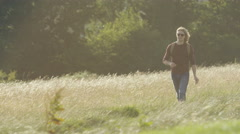 4K Handsome man walking through a meadow on a nice day - stock footage