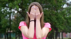 Beautiful Young Girl Playing Hide and Seek Covering Her Face With Her Hands and Stock Footage