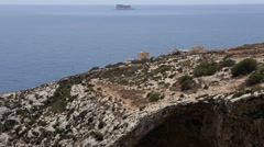 Blue Grotto in Zurrieq, Malta, panning up to the island of Filfla. Stock Footage