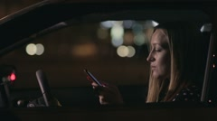 Charming woman texting message on cellphone in car Stock Footage