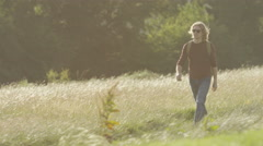 4K Handsome man walking through a meadow, in slow motion - stock footage