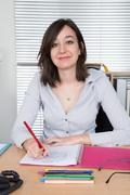 Woman colouring with soft tip pencils at work - stock photo