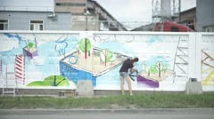 Young creative woman paints the fence of an industrial enterprise. Russian Stock Footage