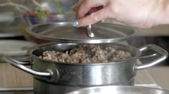 Hand Pours Buckwheat Porridge From the Pot Into the Green Plate. Stock Footage