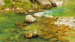 The mountain river flows among stones, water texture Stock Footage