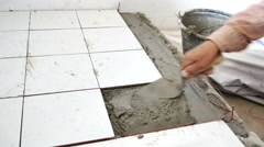 Worker putting ceramist tile on the floor.  Stock Footage
