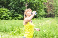 Beautiful fitness athlete woman drinking water after work out exercising outdoor Stock Photos