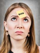Confused woman with a sticker on her forehead - stock photo