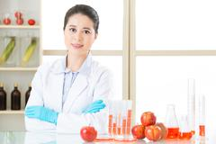 Asian female scientist looking for cure for genetic modification food - stock photo