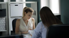 Two women sitting opposite each other at work in office Stock Footage