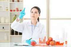 Asian female scientist drop the cure for genetic modification - stock photo