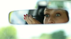 Cute woman applying mascara in car rearview mirror - stock footage