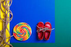 Small red boat shoes near big multi-colored lollipop Stock Photos