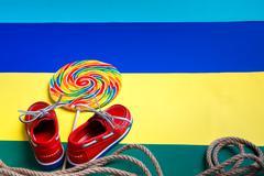 Small red boat shoes near big multi-colored lollipop - stock photo