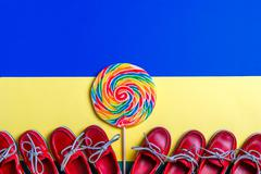 Lot of small red boat shoes near big multi colored lollipop Stock Photos