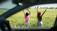 View through car window of women jumping in field Stock Footage