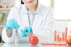 Asian female scientist working on plant biology - stock photo
