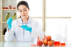 Asian female scientist examining for genetic modification food Stock Photos