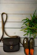Green lacquered oxford shoes and crossbody bag on wooden background near flow Stock Photos