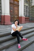 Woman is reading book. Girl with book in white polo, black pant and red shoes - stock photo