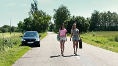 women walking on road with rusty canister in hand - stock footage