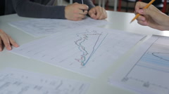 Analysis and discussion of graphs on table, male and female hand with a pencil Stock Footage