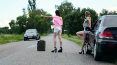 Young women hitchhiking near broken car Stock Footage