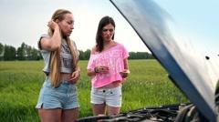 Cute women standing near opened hood of broken car Stock Footage
