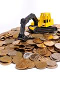 Yellow excavator on a big heap of coins Stock Photos
