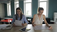 Office staff work in a row at same table, looking at documents, and in tablet Stock Footage
