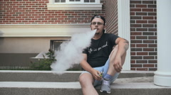 Young Man Sitting Near House On The Street And Smoke E-Cigarette. Vape. Slow-Mo - stock footage