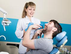 Doctor examines the oral cavity on tooth decay. Caries protection. Tooth decay Kuvituskuvat