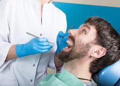Doctor examines the oral cavity on tooth decay. Caries protection. Tooth decay Stock Photos
