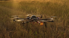 Spinning of drone propellers in field at sunset. Slow motion Stock Footage