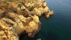 Ponta da Piedade lighthouse on cliff near ocean at sunset, Lagos, aerial view Stock Footage