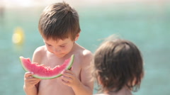 Two little children, boys brothers, eating watermelon on the beach - stock footage