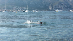 Two cute boys with swimming goggles and snorkel swimming in the sea, French r Stock Footage