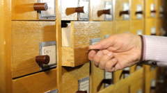 Man Looking For a Book in the Library Card Catalog - stock footage