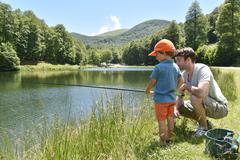 Father and son fishing together by mountain lake Stock Photos