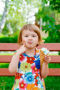 Cute and happy little girl eating ice cream outside. Yummy ice cream - stock photo