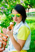 Young girl hold delicious ice cream in summer hot weather wearing yellow and  - stock photo