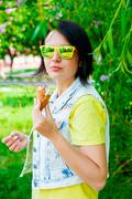 Young girl hold ice cream in summer hot weather wearing yellow and blue cloth - stock photo
