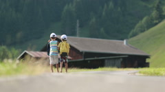 Two little children, boy brothers with backpacks travel on the road to scenic Stock Footage