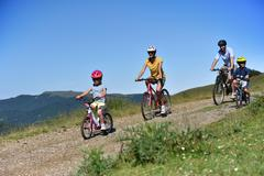 Parents with kids riding bikes in moutain path Stock Photos
