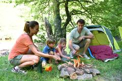 Family camping and cooking sausages in campfire Stock Photos