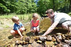 Father and kids in river building a dam with pebbles Stock Photos