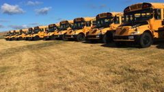 4K UltraHD A Motion controlled pan of two rows of schoolbuses Stock Footage