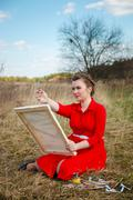 Young artist measures the proportion of the object to draw. Woman in a red dr - stock photo