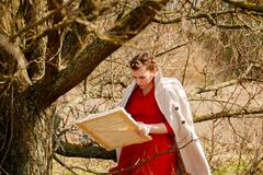 Young artist painting a landscape. Woman in a red dress stand near dry tree i - stock photo
