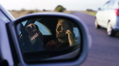 4K View in mirror of frustrated man talking in his car by the roadside Stock Footage